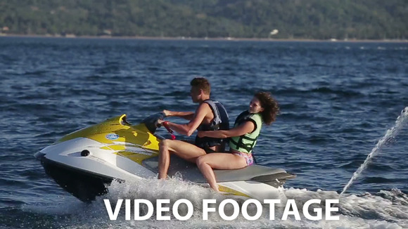 Happy Couple Riding Jet Ski