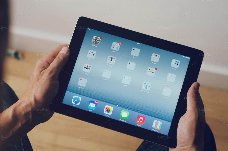 hands holding an apple ipad