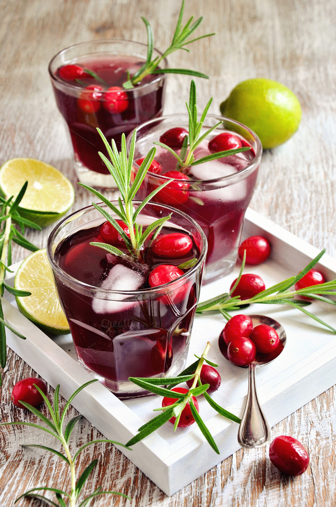 Red refreshing cranberry cocktail with rosemary, lime, and ice cubes ...