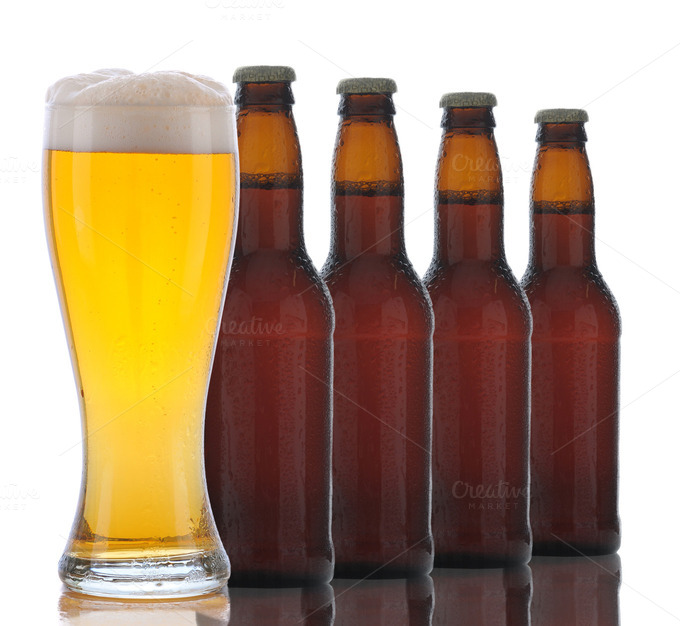 Four brown beer bottles and a full glass of ale on a white background